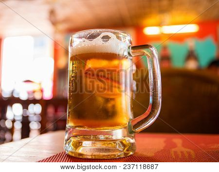 Drinking Beer In Daytime. Transparent Glass Mug With Beer On Wooden Table. Lunch In Cafe With Beer.