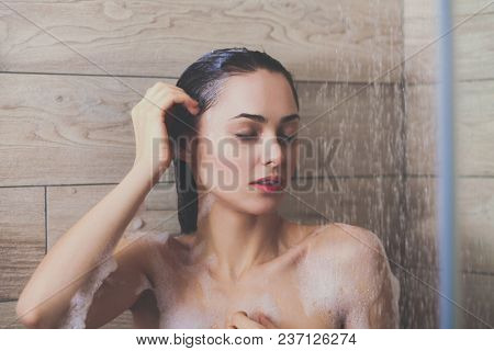 Young beautyful woman under shower in bathroom.