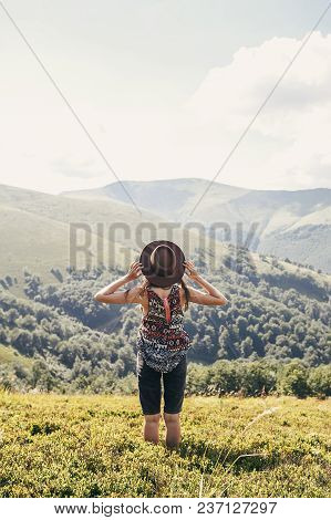 stylish traveler girl in hat looking at sunny mountains. summer vacation. travel and wanderlust concept. space for text. back view. woman traveling. amazing atmospheric moment poster