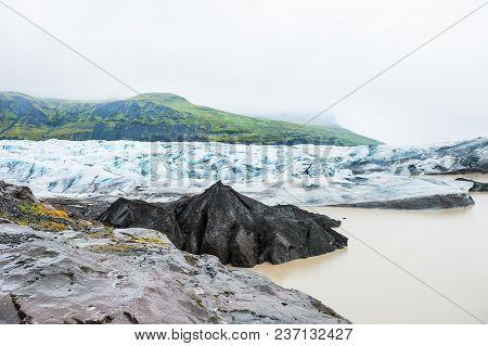 Icebergs With Black Volcanic Ash In Glacier Lagoon, Vatnajokull Glacier In Southern Iceland.
