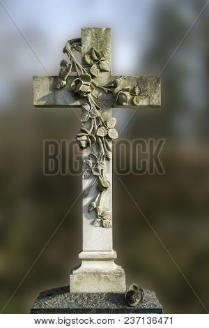 Stone Cross With Roses On A Grave. Outdoor Shot