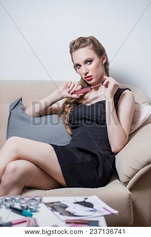 Beautiful Sexy Blonde Girl In Black Short Dress Sitting On The Sofa In The Salon For A Coffee Table