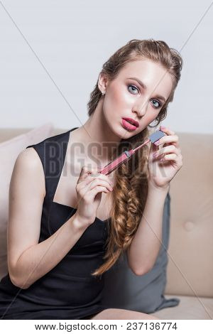 Beautiful Sexy Blonde Girl In Black Dress Sitting On The Sofa In The Salon With Lipstick On His Hand