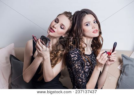 Two Beautiful Girls Sitting On The Sofa, Makeup, Looks At The Mirror, Causing A Pink Red Lipstick, L