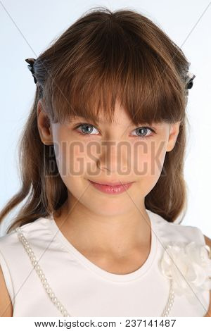Close-up Portrait Of A Beautiful Girl In A White Blouse. Charming Happy Attractive Child Smiling. Th