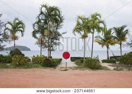 Entrance To White Sand Beach With Blank Red Sign. Park And Sea View With Palm Trees. Hotel Or Resort