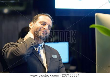 Tired Neck. Hotel Manager. A Men-reception Suffering From Neck Pain. Bearded Man. Male Feeling Tired