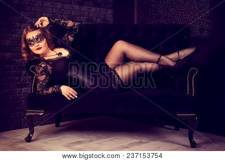 Beautiful Young Woman In Mask And Corset Lies On Sofa. Vintage Retro Background. Retro Glamor Vintag