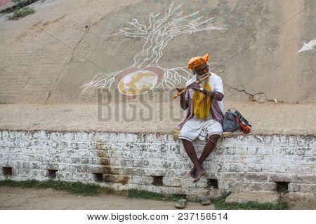 VARANASI, INDIA - MAR 15, 2018: Pilgrim expect ritual  Agni Pooja (Sanskrit: Worship of Fire) on Dashashwamedh Ghat - main and oldest ghat of Varanasi located on the Ganges.