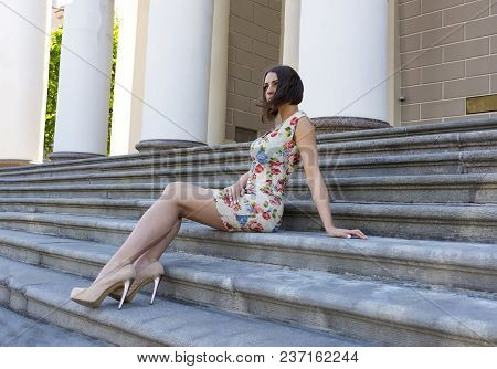 Slender, Beautiful Girl In A Short Dress With Floral Print In High Heels Sitting On The Stairs, Port