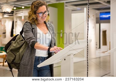 Woman with phone configuring furniture at the self-service device in the store poster