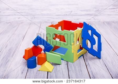 Edicational Games For Children. Red, Yellow, Pink, Blue Geometrical Figures On The Wooden Background