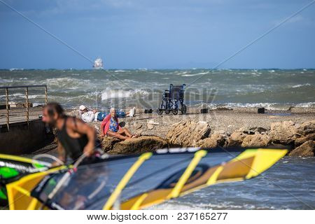 Livorno, Italy - August 2017: Old Woman Sitting On The Rocks Near Coastline Looks At Young Surfer On