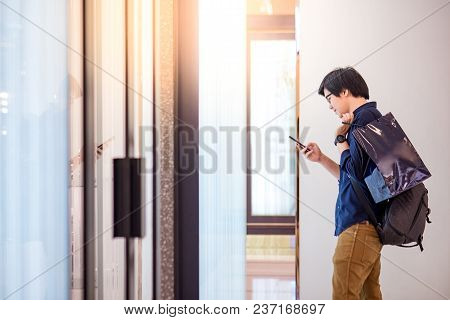 Young Asian Man Dressed In Casual Style Holding Blue Shopping Bag Using Smartphone Near Retail Wall