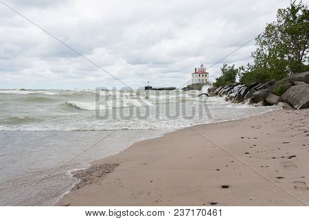 Lighthouse At Mentor Headlands Beach State Park In Ohio With Waves Crashing On Shore And Dark Clouds