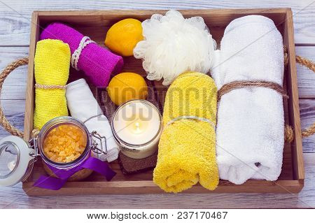 Spa Consist From Towels, Yellow Sea Salt And Other Accessories For Bath In A Wooden Tray
