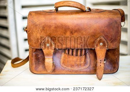 Brown Vintage Leather Briefcase With Strap And Brass Buckle.