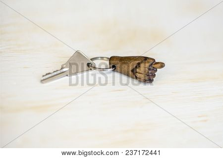 Symbol Of A Fig Gesture With A Silver Key On A White Wooden Background Background.