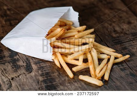 French Fries Potatoes In A Paper Bag On Wood Background