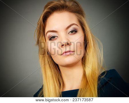 Portrait Of Feminine Blonde Young Woman Wearing Dark Top Shirt Having Serious, Proud Look Face Expre