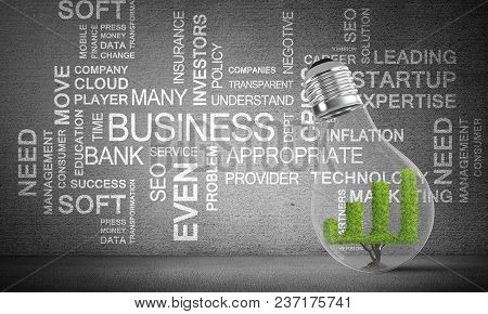 Glass Lightbulb With Growing Green Graph Inside Placed Against Business Related Terms On Grey Wall O