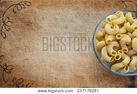 Raw Cavatappi Pasta In A Glass Cup On A Cutting Wooden Board, Textured Background With A Side. Close