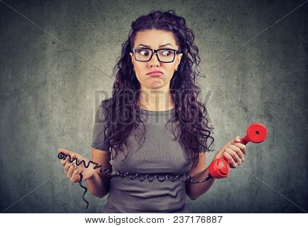 Young Woman Looking With Bewilderment Holding Old Fashioned Red Handset.
