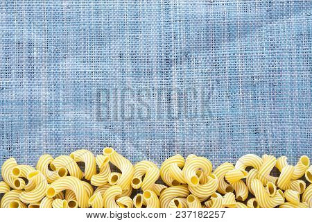 Raw Cavatappi Beautiful Decomposed Pasta With A Bottom On A Rustic Blue Knitted Sack Texture. Close-