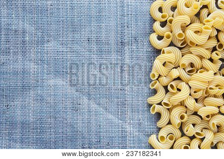 Raw Cavatappi Beautiful Decomposed Pasta With The Right, On Its Side On A Rustic Blue Knitted Sack T