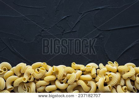 Raw Cavatappi Beautiful Decomposed Pasta With A Bottom On A Black Textured Background. Close-up View