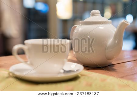 Hot Tea Cup With Spoon On White Plate, White Kettle, Cafe Blurred On Background, Breakfast Concept.