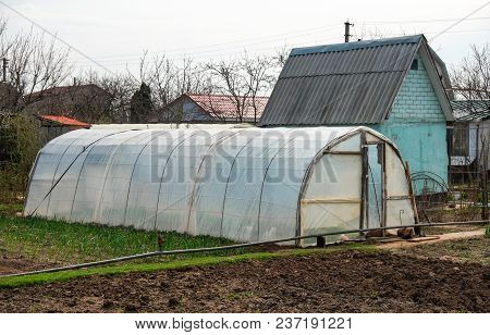 Vegetable Patch With Seedlings Covered With Spunbond And Polyethylene Film To Keep Humidity And Agai