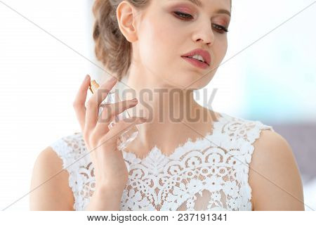 Beautiful Young Bride With Bottle Of Perfume On Blurred Background, Closeup