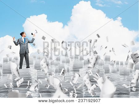 Businessman In Suit Standing On Pile Of Documents Among Flying Papers With Speaker In Hand With Clou