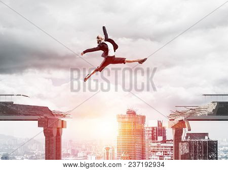 Business Woman Jumping Over Gap In Concrete Bridge As Symbol Of Overcoming Challenges. Sunlight And