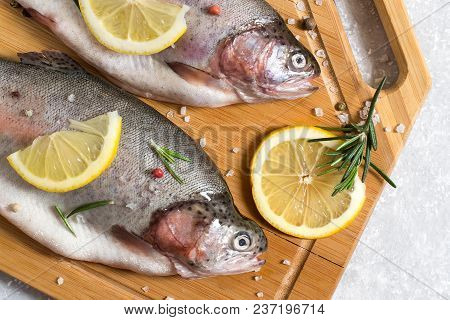 Two Fresh Trout On Cutting Board And Ingredients For Cooking (pepper, Salt, Lemon, Seasoning And Ros