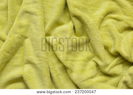 Soft Green Fabric With Waves And Folds. Soft Textile Texture. Folds On The Soft Fabric.