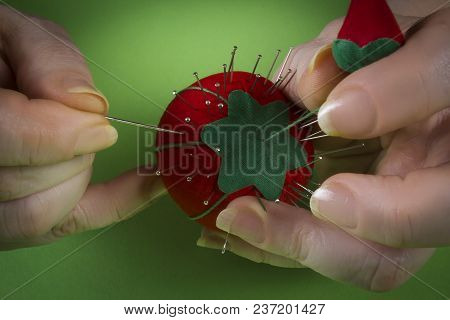 Hands Of A Woman Tailor With Needles On A Green Background