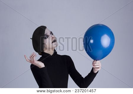 Mime Girl With A Blue Balloon On A Gray Background