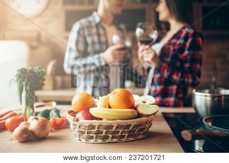 Basket of fresh fruits, love couple drinking  wine