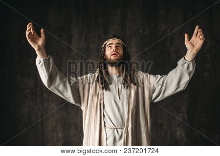 Jesus Christ in white robe prays with his hands up