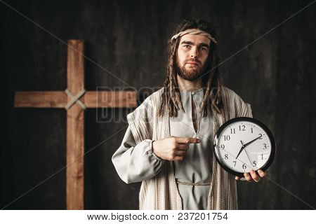 Man in the image of Jesus Christ shows on clock