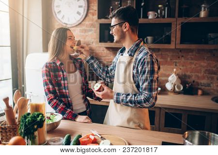 Husband feeds wife a banana on the kitchen