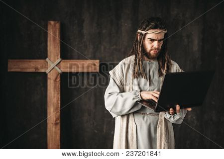Man in the image of Jesus Christ uses laptop