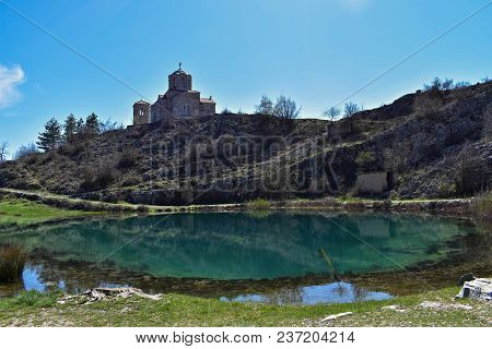 Mountain River And Lake With Spring Green Hills And Mountains Against Blue Skies/orthodox Church And