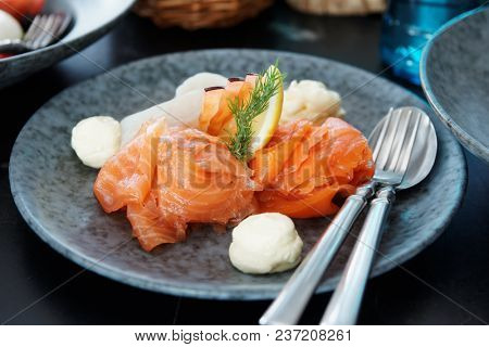 Salted and smoked salmon in gray stoneware plate on restaurant table