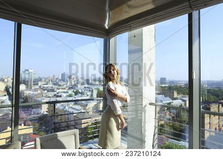 Charming Woman Standing At Restaurant Near Window With Buildings In Background. Concept Of Catering