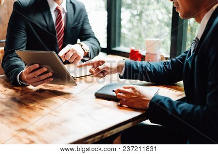 Two Businessman Sitting And Looking At Tablet, They Are Meeting About Business Plan, Marketing And F