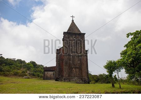 Old Abandoned Church In Green Field. Medieval Ruin In Summer Landscape. Christian Temple From Brown