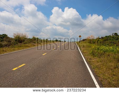 Empty Road To Cloudy Sky. Straight Road In Green Hills. Tropical Roadside. Turn Right Sign. Summer O